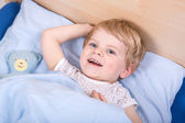 Cute blond toddler boy in bed — Stock Photo