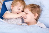 Two little toddler boys having fun in bed — Stock Photo