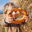 Little boy eating German pretzel on goden hay field — Stock Photo #25261653
