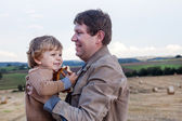 Young father and adorable little son hugging on straw field — Stock Photo