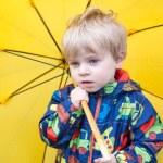 Cute toddler boy with yellow umbrella, outdoors — Stock Photo #25749709