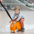 Toddler boy sitting on a suitcase at airport — Stock Photo