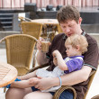 Young man and his little son sitting at the table in restaurant — Stock Photo