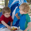 Two little boys eating french fries in summer — Stock Photo #26818881