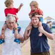 Grandfather and father giving two boys ride on shoulders — Stock Photo