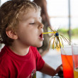 Happy little boy drinking orange juice with straw — Stock Photo