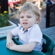 Portrait of beautiful little toddler boy sitting in outdoor rest — Stock Photo