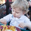 Cute little boy eating french fries in summer — Stock Photo