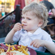 Cute little boy eating french fries in summer — Stock Photo #26934277