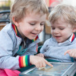 Stock Photo: Two brother toddler boys playing with tablet pc
