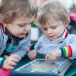Two brother toddler boys playing with tablet pc — Stock Photo