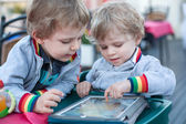 Two brother toddler boys playing with tablet pc — Stockfoto