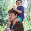 Happy Young father giving little boy a ride on shoulders — Stock Photo