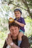 Glad ung pappa ger liten pojke en tur på axlarna — Stockfoto