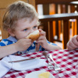Little toddler boy having breakfast in summer — Stock Photo