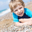 Little toddler boy playing with sand and stones on the beach — Stock Photo