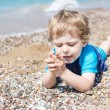 Little toddler boy playing with sand and stones on the beach — Stock Photo #27117983