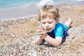 Kleine kleinkind jungen spielen mit sand und steinen am strand — Stockfoto