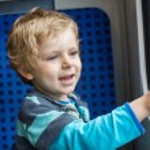 Cute little boy looking out train window — Stock Photo #27152983