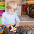 Little toddler boy playing with wooden toys — Stockfoto