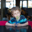 Little blond boy sitting on high chair in cafe with cocktail — Stock Photo