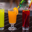 Colorful cocktails with straw on wood table — Stock Photo #27859317