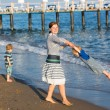 Happy mother and two little children walking on the beach — Stock Photo