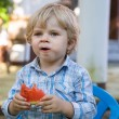 Adorable little toddler boy with blond hairs eating watermelon i — Stock Photo