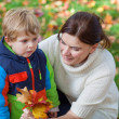 Little toddler boy and young mother in the autumn park — Stock Photo #28419265