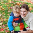 Little toddler boy and young mother in the autumn park — Stock Photo #28419537