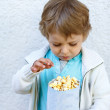 Happy little boy with popcorn bag — Stock Photo