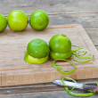 Fresh green limes on wooden old table — Stock Photo