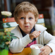 Adorable little boy eating frozen yoghurt ice cream in cafe — Stockfoto #28955173