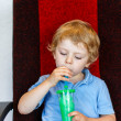Stock Photo: Little boy drinking colorful frozen slush ice