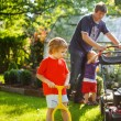 Man and two little sibling boys having fun with lawn mower — Stock Photo