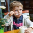 图库照片: Adorable little boy eating frozen yoghurt ice cream in cafe