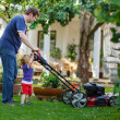 Man and his little son having fun with lawn mower in garden — Stock Photo