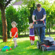 Stock Photo: Mand two little sibling boys having fun with lawn mower