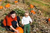 Little toddler boy and his mother on pumpkin field — Stock Photo