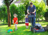 Man and two little sibling boys having fun with lawn mower — Стоковое фото