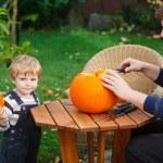 Young man and toddler boy making halloween pumpkin — Stock Photo