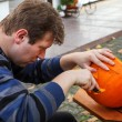Stock Photo: Young mmaking halloween pumpkin
