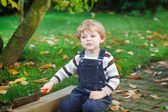 Little toddler boy playing in autumn garden — Stock Photo