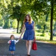 Stock Photo: Beautiful mother and little daughter walking in summer park