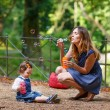 Stock Photo: Beautiful mother and little daughter blowing soap bubbles in sum