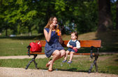 Beautiful mother and adorable daughter blowing soap bubbles in sum — Stock Photo
