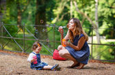 Beautiful mother and little daughter blowing soap bubbles in sum — Stock Photo