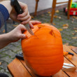 Stock Photo: Hollowing out pumpkin to prepare halloween lantern