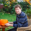 Young man making halloween pumpkin — Stock Photo #30370121