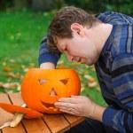 Young man making halloween pumpkin — Stock Photo